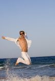 Happy smiling Man jumping on beach Stock Photography