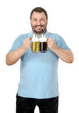 Portrait of cheerful bartender. Holding light and dark beer tankards Royalty Free Stock Photos