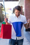 A happy smiling man looking into his shopping bags Stock Photos