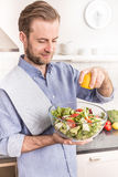 Happy smiling man making fresh vegetable salad in the kitchen Royalty Free Stock Photo