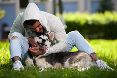 Happy smiling man playing with husky dog in park Stock Photos