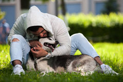 Happy smiling man playing with husky dog Royalty Free Stock Photo
