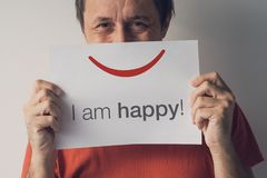 Happy smiling man, real people portraits. Adult caucasian male hiding behind paper with smiley emoticon and text I am Happy Stock Photography