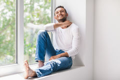 Happy smiling man relaxing on window sill Royalty Free Stock Images