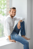 Happy smiling man relaxing on window sill Stock Photography