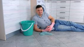 Happy smiling man in rubber gloves has a rest from cleaning laying on the kitchen floor. stock video