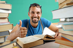 Happy smiling man showing thumbs up gesture in surrounded by books Royalty Free Stock Image