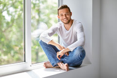Happy smiling man sitting on window sill in lotus pose Royalty Free Stock Photo