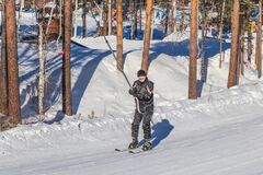 Happy smiling man in a ski suit climbs the mountain on skis on a snow-covered slope using a drag lift