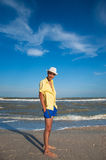 Happy smiling man. Summer mood. Happy young man in hat, blue shorts and yellow shirt standing on the beach near the sea and smiling. Summer mood Stock Image