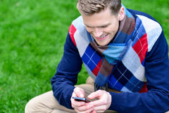 Happy smiling man using mobile phone on park Stock Photos