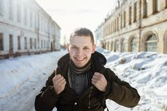 A happy smiling man wearing a fur trendy warm scarf posing in the city. A happy smiling man wearing a fur trendy warm scarf posing in the winter city. Man holds Stock Image