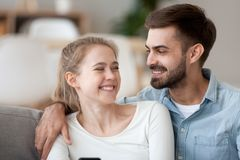 Happy smiling man and woman cuddle, using phone together. Happy smiling man and woman cuddle sitting on cozy sofa, laughing at online joke, funny news in social stock images