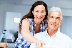 Mature couple looking at camera. Happy smiling mature couple at home royalty free stock photography