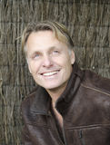 Happy smiling mature man with blond hair. Wearing a brown leather jacket Royalty Free Stock Photography