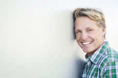 Happy smiling mature man in forties. Color portrait photo of a happy laughing blond haired man in his forties wearing a green checked shirt and leaning against Royalty Free Stock Photography