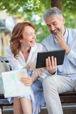 Happy smiling mature tourists sitting on a bench looking at a tablet and laughing royalty free stock photography