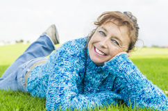 Happy smiling mature woman laying on grass Stock Photo