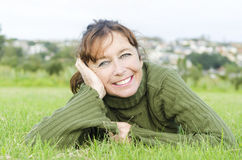 Happy smiling mature woman laying on grass Stock Photos