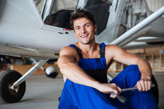 Happy smiling mechanic in overall resting after hard working day. Holding wrench Stock Photography