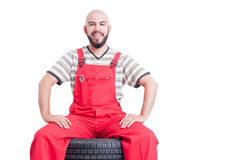 Happy smiling mechanic sitting on stack of car wheels. Isolated on white Stock Photography