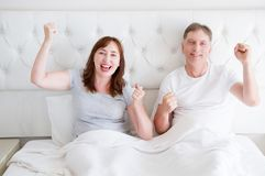 Happy smiling middle age couple in bed in t shirt. Healthy family relationships. Copy space stock image
