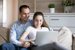 Happy smiling millennial couple watching video on computer at home stock photo