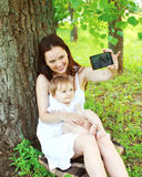 Happy smiling mom and baby taking self-portrait on smartphone Stock Image