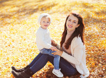 Happy smiling mom with little child playing in autumn park Stock Photography