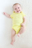 Happy smiling 2 months baby girl in yellow bodysuit Royalty Free Stock Photos