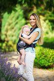 Happy smiling mother with baby boy in sling walking in green park Royalty Free Stock Photography