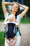 Happy smiling mother with baby boy in sling walking in green park Royalty Free Stock Photo