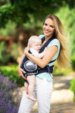 Happy smiling mother with baby boy in sling walking in green park Royalty Free Stock Images