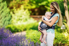Happy smiling mother with baby boy in sling walking in park Stock Image