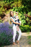 Happy smiling mother with baby boy in sling walking in park Royalty Free Stock Images