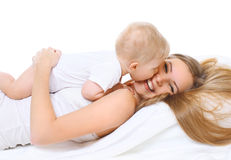 Happy smiling mother and baby playing on bed Royalty Free Stock Images