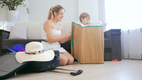 Happy smiling mother with baby son playing while packing suitcase for summer holiday stock video