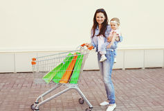 Happy smiling mother and baby with trolley cart and shopping bags Royalty Free Stock Photography