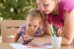 Happy Smiling Mother And Child Daughter Drawing Picture. Happy Smiling Mother And Child Daughter Having Fun and Drawing Pictures Outdoors in Garden in Summer royalty free stock images