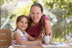 Happy Smiling Mother And Child Daughter Drawing Picture stock photo
