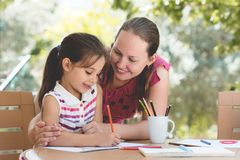 Happy Smiling Mother And Child Daughter Having Fun and Drawing Pictures Outdoors royalty free stock images