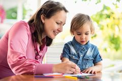 Happy Smiling Mother And Child Daughter Having Fun and Drawing Pictures in Garden in Summer Season. Happy Smiling Mother And Child Daughter Having Fun and royalty free stock images