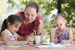 Happy Smiling Mother And Child Daughters Drawing Pictures stock photo