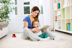 Happy smiling mother and child playing on tablet Royalty Free Stock Images