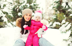 Happy smiling mother with child on snow in winter. Day Stock Photo
