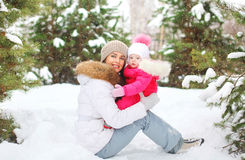 Happy smiling mother with child in snowy winter day. On snow Royalty Free Stock Photo