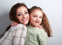 Happy smiling mother cuddling playful emotional fun daughter in Stock Images