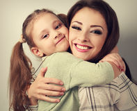 Happy smiling mother cuddling playful emotional kid girl in stud. Io. Toned closeup portrait Stock Photography