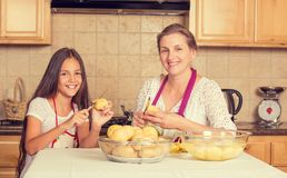 Happy, smiling mother and daughter cooking dinner Stock Photos
