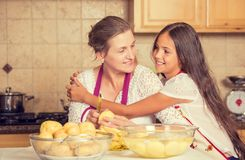 Happy, smiling mother and daughter cooking dinner, preparing food Royalty Free Stock Images